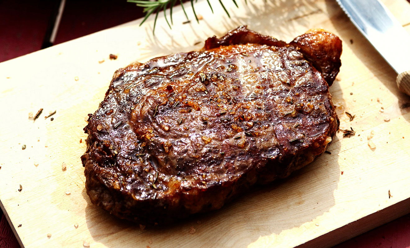 Organic Grass finished ribeye steak marinated with Honey and ginger on a wood cutting board