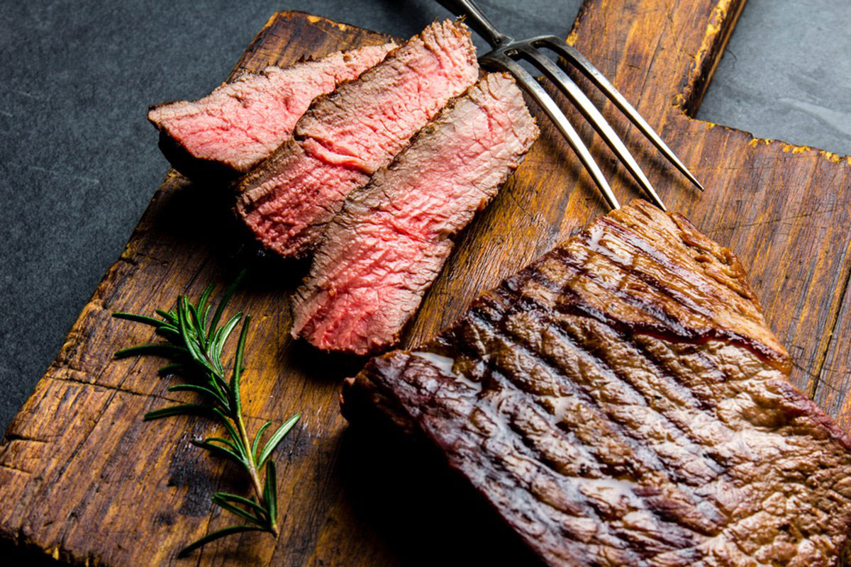 Organic Grass Fed beef flank steak on a rustic wooden cutting board with rosemary