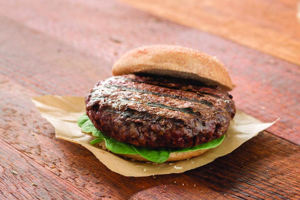organic grass fed beef burger patties on wood table