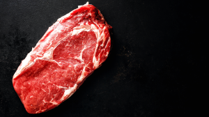 organic, grass fed cut of beef on black background
